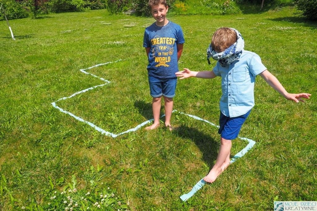 dzieci bawia sie w ogrodzie, dziecko z zawiązanymi oczami pokonuje wyklejoną na trawie trasę, zabawy w ogrodzie, kodownie dla dzieci