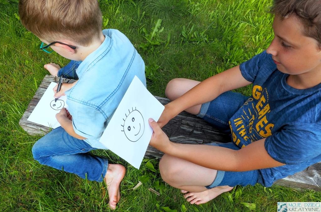 zabawy w kodowanie dla dzieci, nauka kodowania, zabawy w ogrodzie, zabawy w przedzkolu i szkole, kodowanie offline, dziecko rysuje na plecach drugiego dziecka.