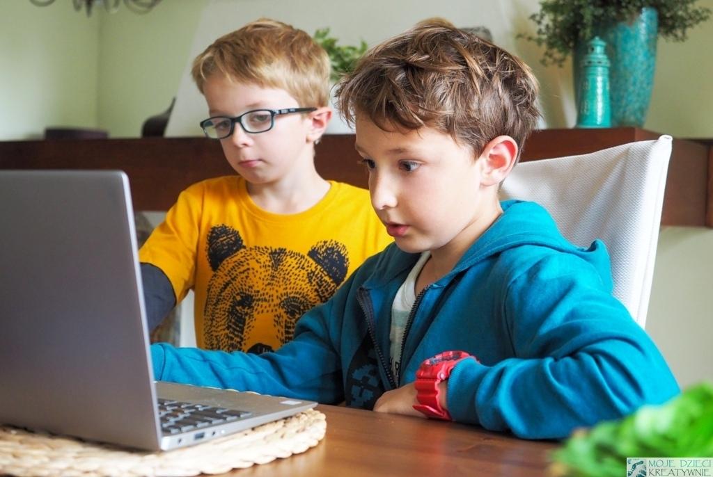 dwóch chłopców przy laptopie czyta wiadomości dotyczące nauki programowania
