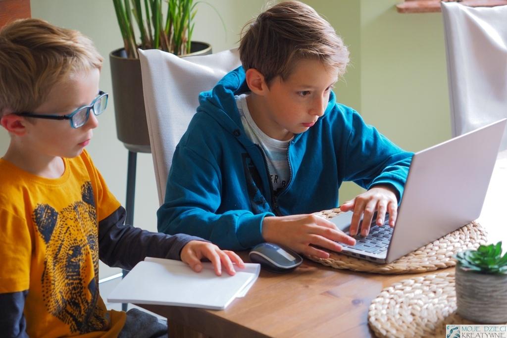 nauka kodowania dla dzieci, dwoje dzieci siedzi przy laptopie i uczy się programowania.