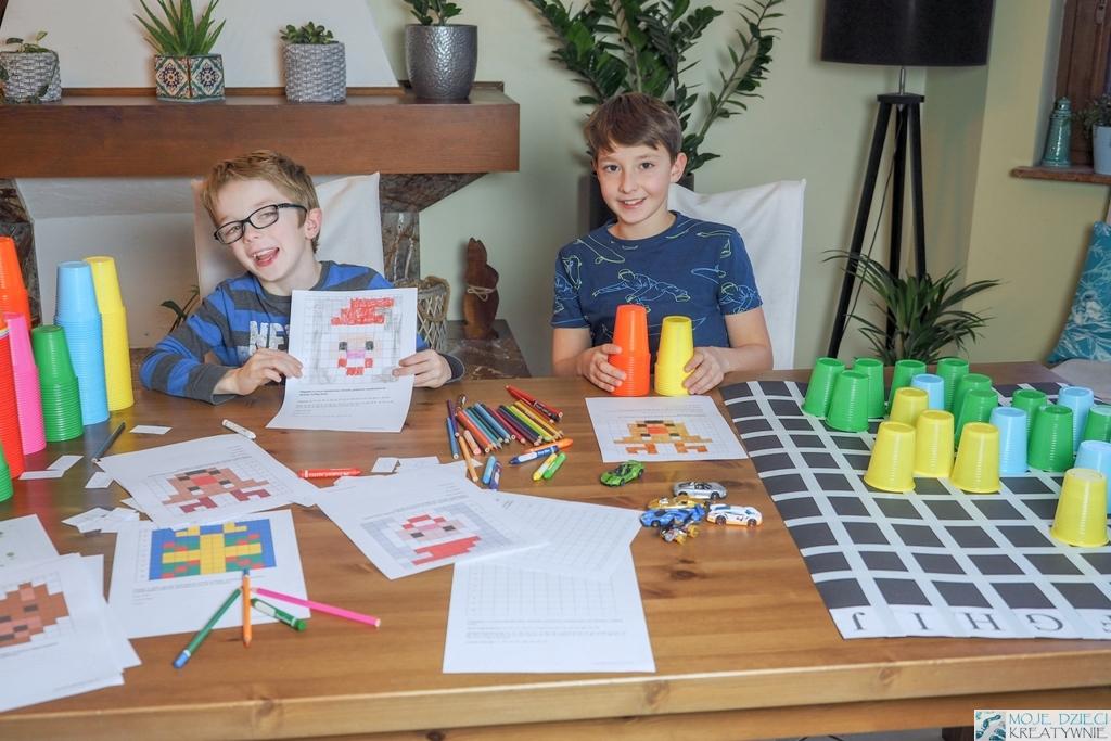 nauka kodowania dla dzieci, na stole leżą zakodowane obrazki, kolorowe kubeczki, plansza do nauki kodownia, dzieci uśmiechają się i pokazują zakodowane obrazki.