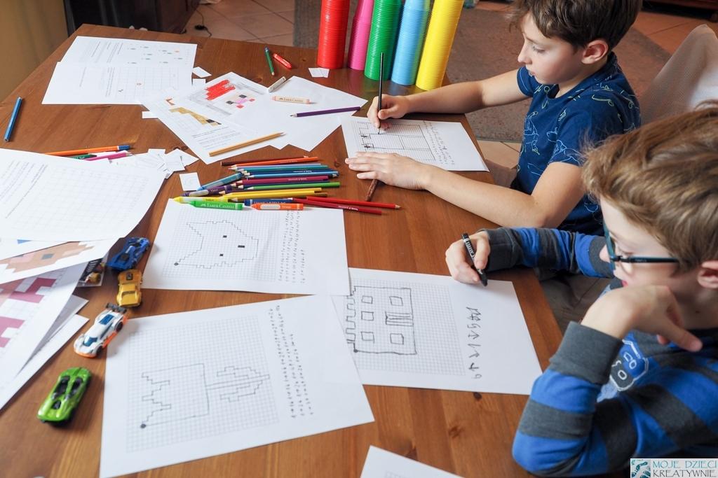 zakodowane obrazki, nauka kodowanie w zabawie, nauka programowania dla dzieci, chłopcy siedzą przy stole i kodują obrazki.