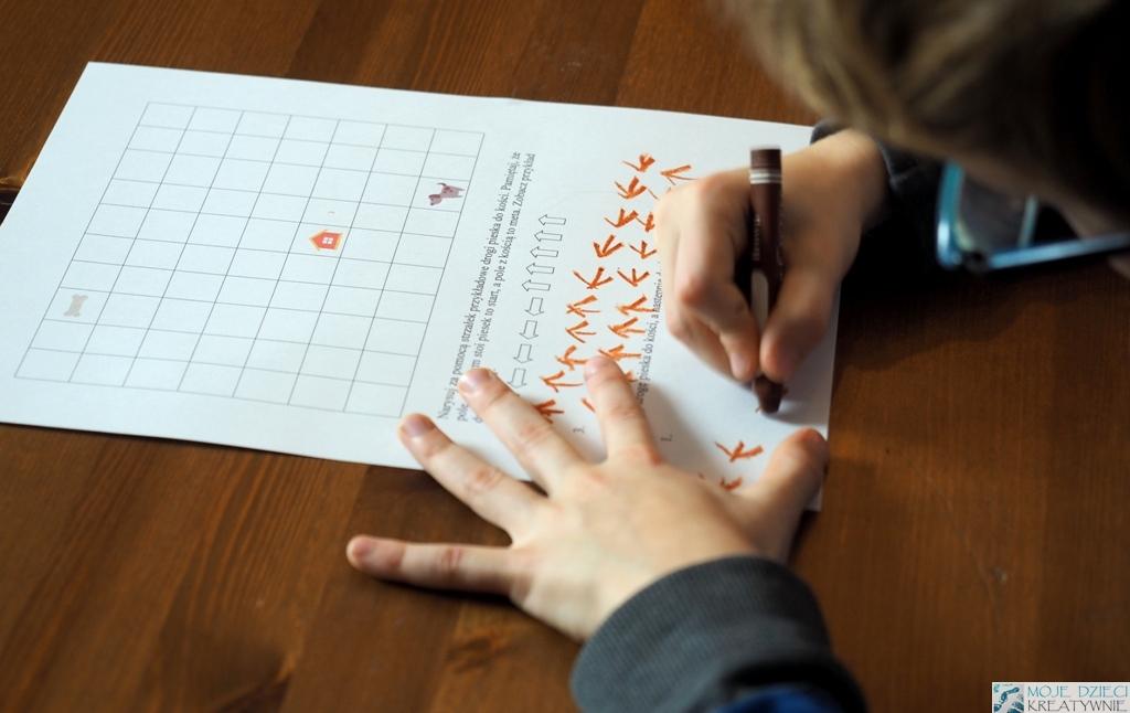 szablon do nauki kodowania z pieskiem, domkiem i kością przedstawiony na planszy, dziecko uczy się kodowania na karcie.