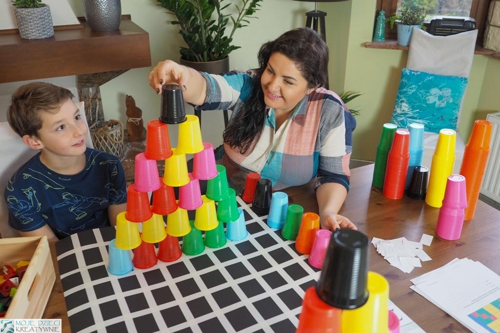 nauka kodowania z kolorowymi kubeczkami, ustawianie muru z kolorowych kubeczków, przy stole siedzi mama i dziecko i bawia się razem w kodowanie za pomocą kolorowych kubeczków.