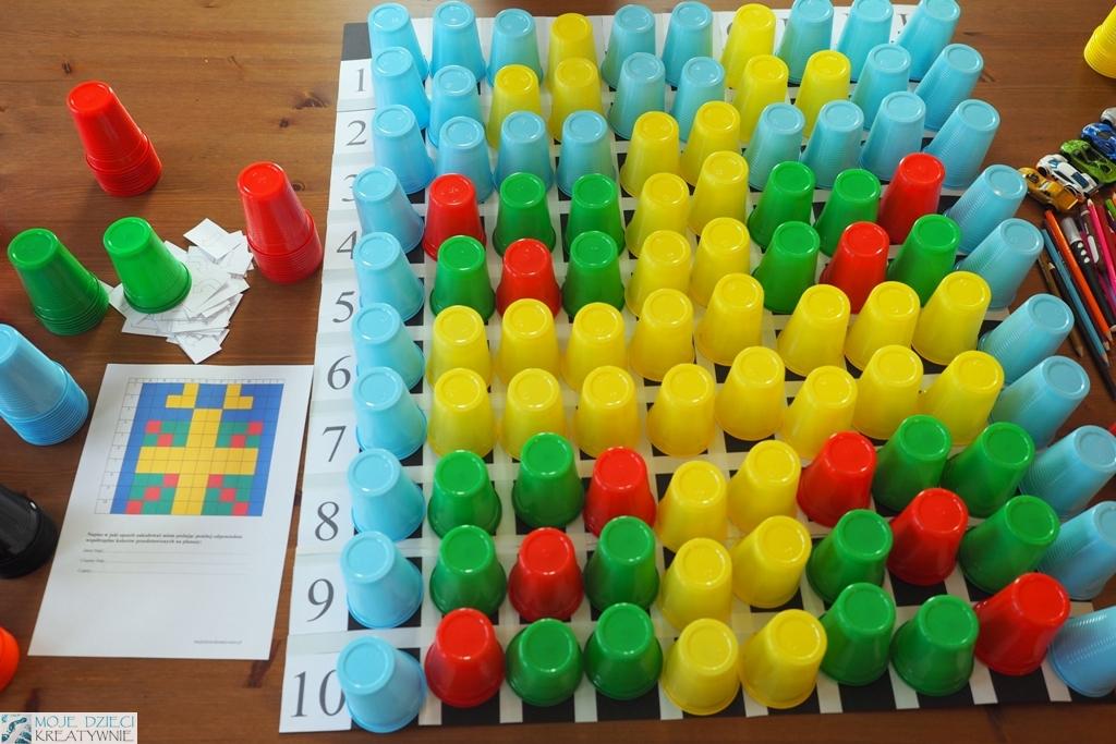 nauka kodowania i programowania poprzez zabawę, plansza do kodowania z kolorowymi kubeczkami, zadkodowny obrazek, zakodowany prezent, kodowanie za pomocą kolorowych kubeczków.