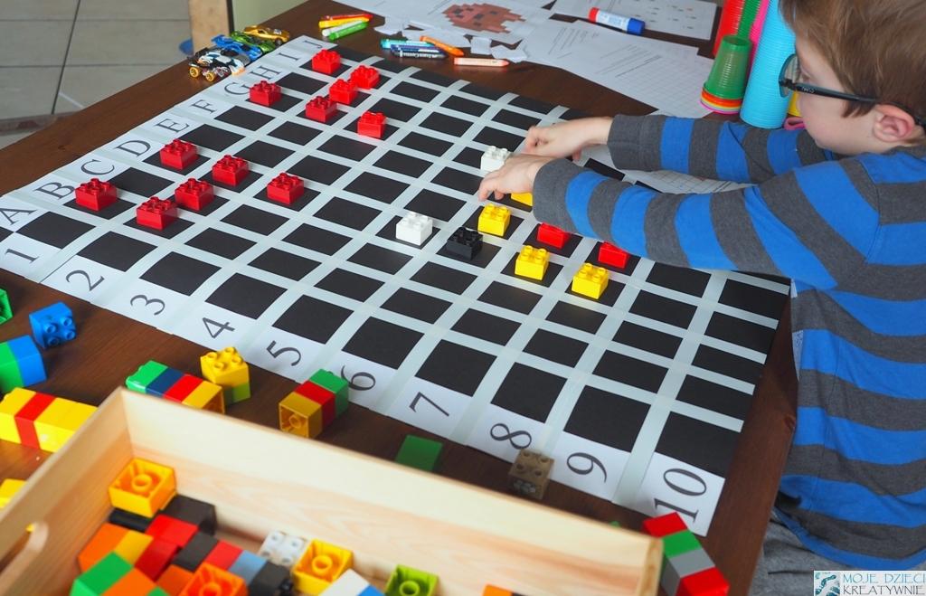 nauka kodowania dla dzieci, chłopiec układa klocki na planszy do nauki kodowania, kodowanie przez zabawę.