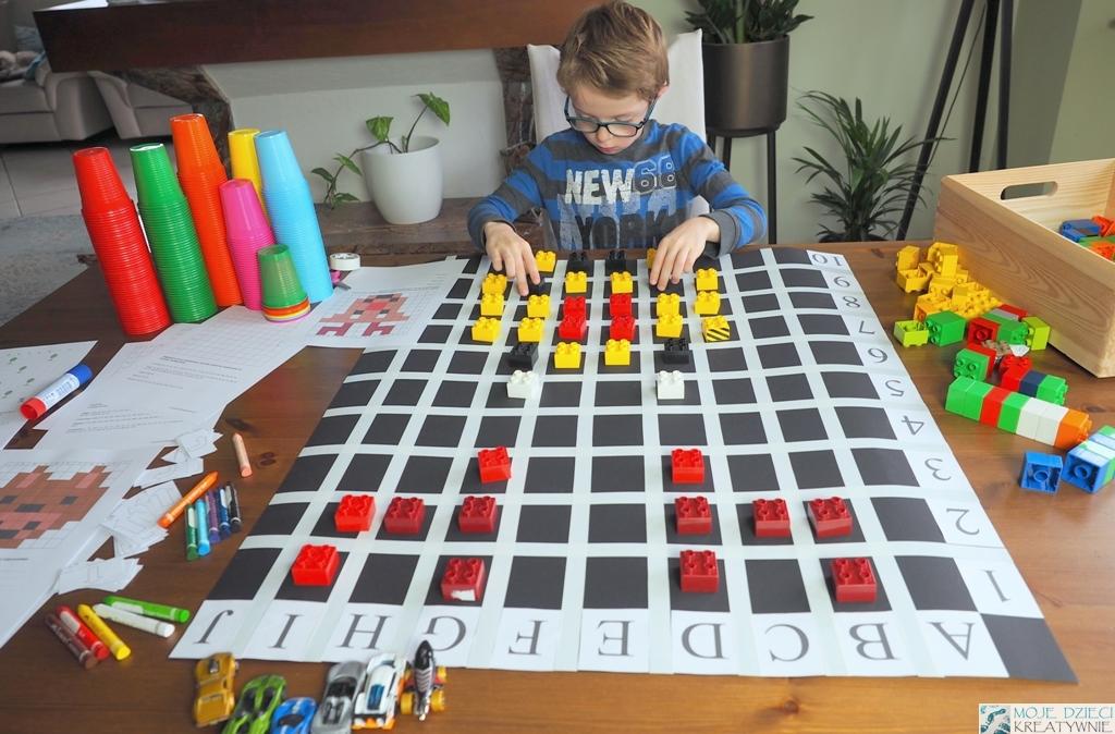 nauka kodowania przez zabawe, kodowanie na planszy za pomocą klocków, dziecko układa klocki na planszy do kodowania, kolorowe kubeczki do kodowania.
