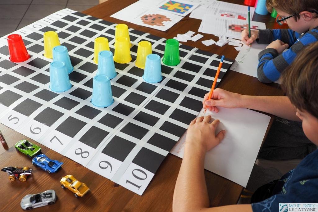 plansza do nauki kodowania, kolorowe kubeczki ułożone na planszy do kodowania, nauka kodowania dla dzieci.