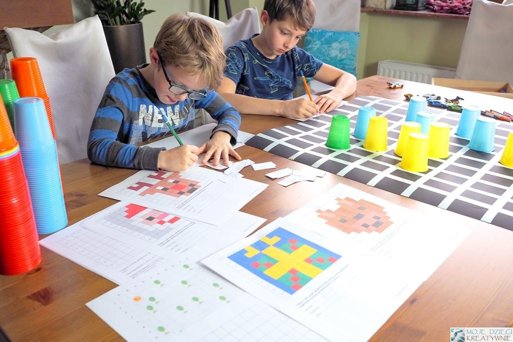 dzieci siedzą przy stole i ucza się kodowania, kolorowe kubeczki do kodowania, zakodowane obrazki