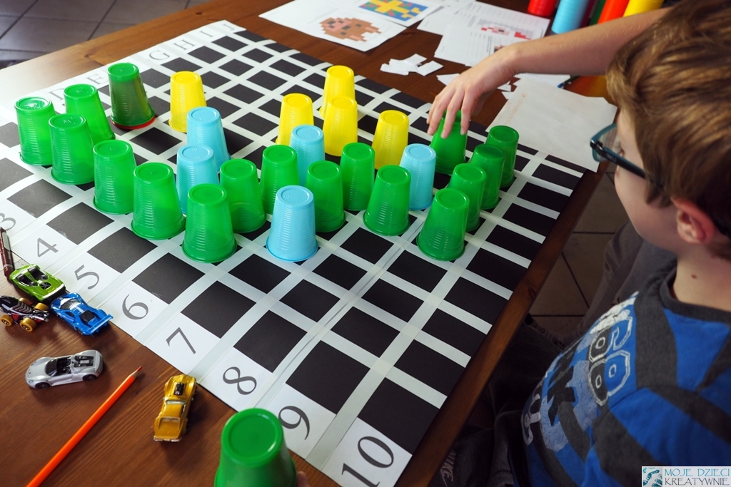 nauka kodowania dla dzieci na planszy za pomocą kolorowych kubeczków, dzieci uczą się kodowania poprzez zabawy.