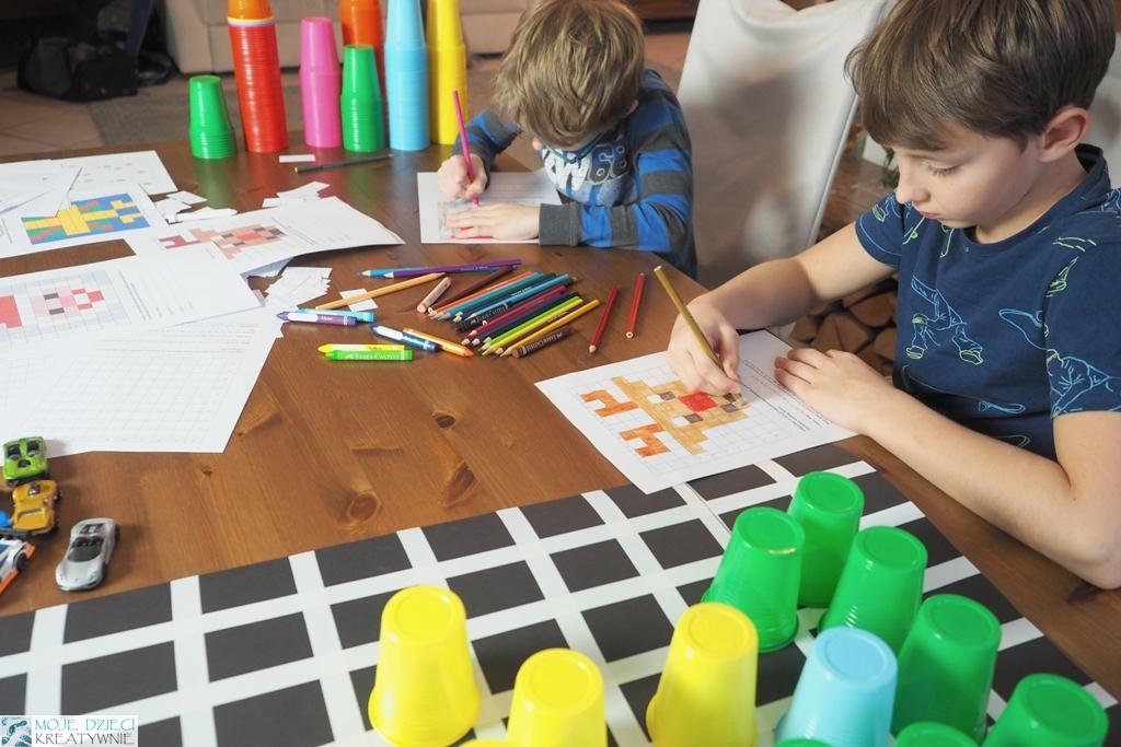dzieci siedzą przy stole i odkodowują obrazki, nauka kodowania w zabawie.