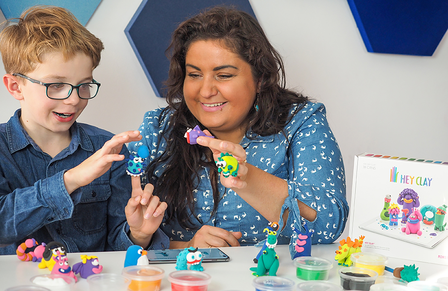 zabaw z dzieckiem, lepienie z masy plastycznej hey clay, uśmiechnięte dziecko i mama trzymają w ręku figurki ulepione z samoutwardzalnej masy plastycznej