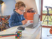 nauka online, dzicko siedzi przy biurku z laptopem i uczy sie angielkiego na platformie novakid