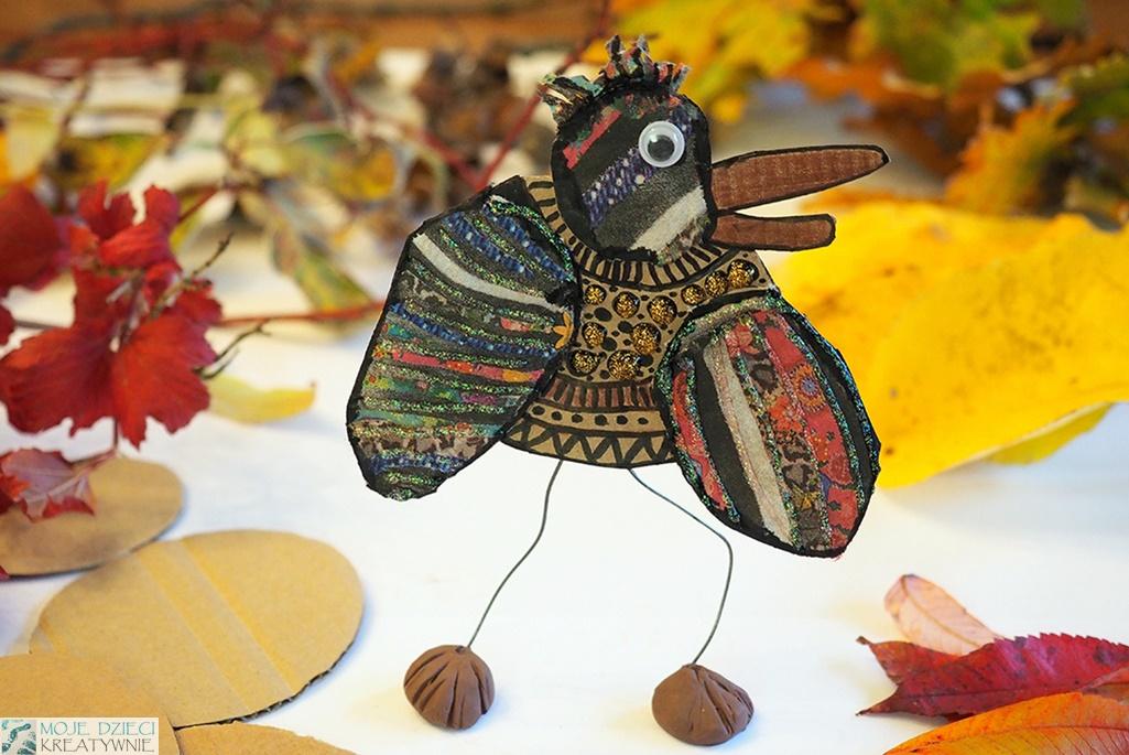 kreatywne pomysły na prace plastyczne w przedszkolu i szkole, ptak z papieru ozdobiony brokatem na nogach z drucika, praca przestrzenna.